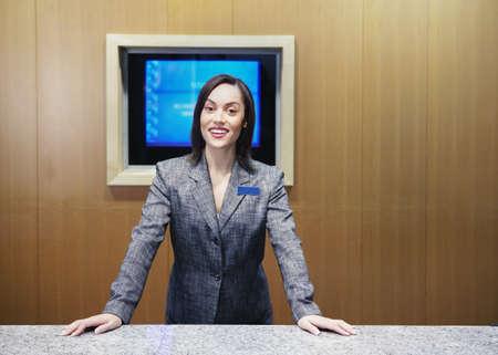 Businesswoman standing behind desk Stock Photo