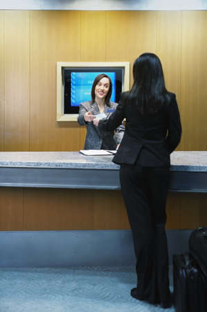 above 25: Hotel clerk assisting customer