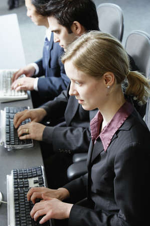 Three businesspeople using computers Stock Photo - 16070404