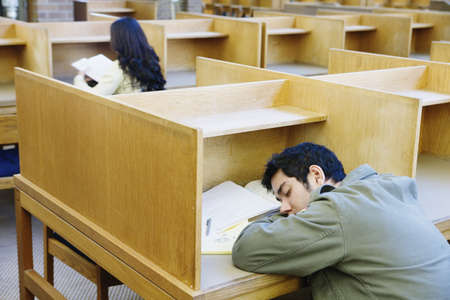 above 18: Male college student napping in library LANG_EVOIMAGES