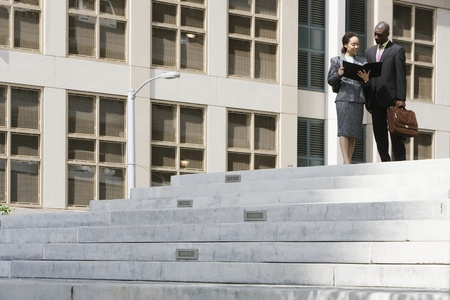 Two businesspeople talking on steps LANG_EVOIMAGES