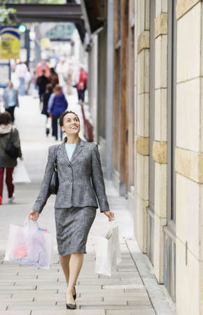 Woman outdoors carrying shopping bags Stock Photo - 16070439