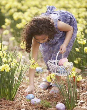 Girl collecting Easter eggs from a field Stock Photo - 16070460