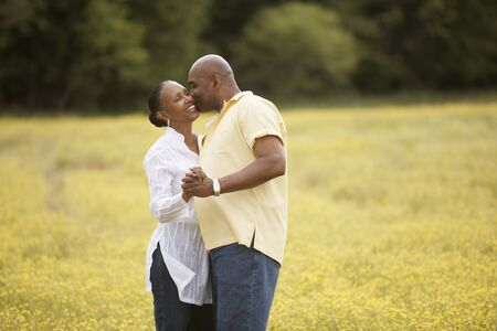 minority couple: Couple dancing together in field
