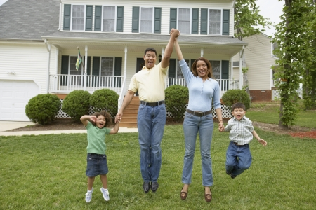 Family jumping together in front yard 스톡 콘텐츠