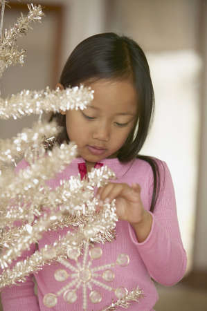 all under 18: Young girl looking at Christmas tree