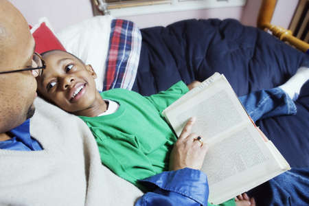 diverse family: Father reading book to son LANG_EVOIMAGES