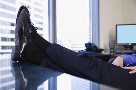 settle back: Feet resting on desk