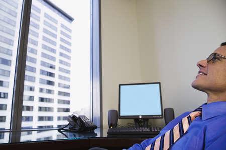 settle back: Businessman sitting at desk LANG_EVOIMAGES