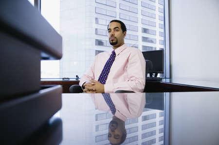 office desk: Businessman sitting behind desk LANG_EVOIMAGES