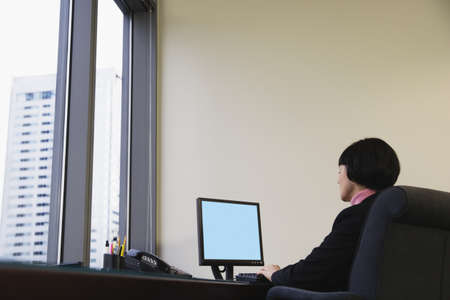 Businesswoman at desk using computer Stock Photo - 16070555