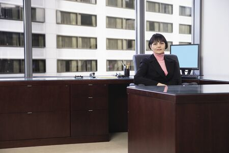 Businesswoman sitting at desk Stock Photo - 16070556