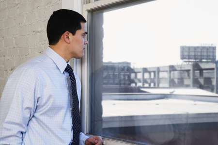 window: Businessman looking out window LANG_EVOIMAGES