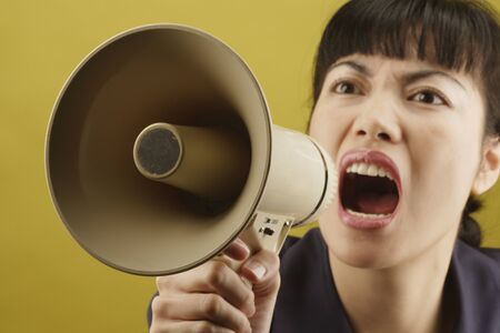 above 25: Close-up of a young woman shouting on a megaphone