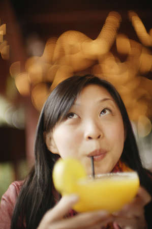 above 25: Close-up of a young woman drinking juice
