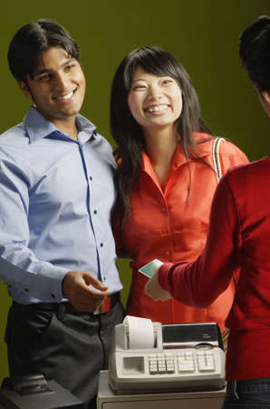 Young couple standing at a checkout counter smiling Stock Photo - 16070626