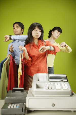 maquina registradora: Dos jóvenes mujeres y un hombre joven que espera en la cola de una caja registradora