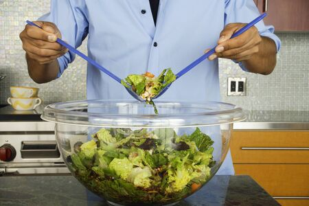 Man in kitchen tossing salad Stock Photo