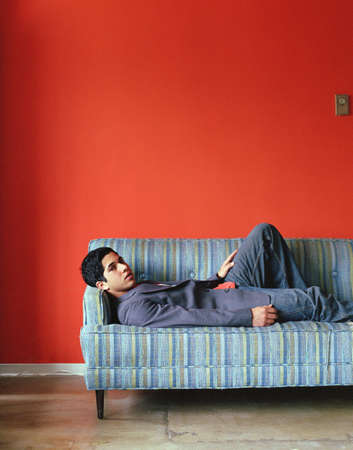 couch: Young man lying down on couch