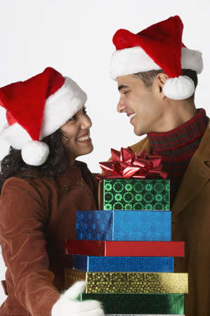 Young couple wearing Santa hats with gifts Stock Photo - 16070698