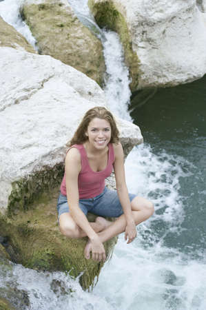Woman sitting on a rock next to water Stock Photo - 16070743