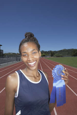 Female athlete showing her blue ribbon Stock Photo - 16070752