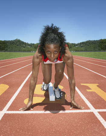 Female track athlete poised at starting line Stock Photo - 16070758