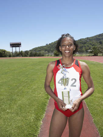 Winning female track athlete holding trophy Stock Photo - 16070764