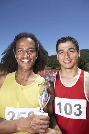 Two male track athletes holding trophy Stock Photo - 16070768