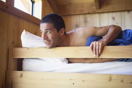 Young man waking up in bunk bed Stock Photo - 16070804