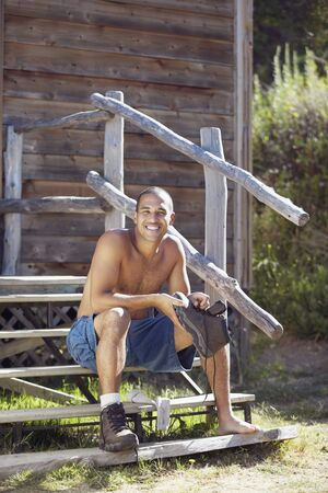 Bare chested man sitting on cabin steps Stock Photo - 16070807