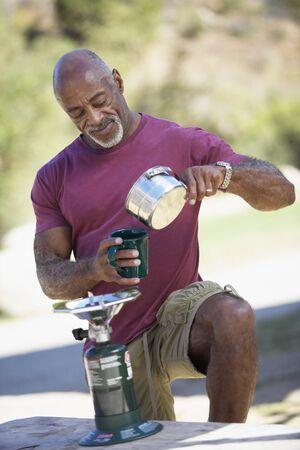 Man on camping trip pouring morning tea