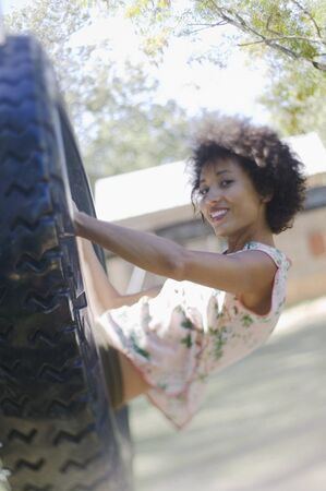 Woman sitting in a playground tire swing Stock Photo - 16070838