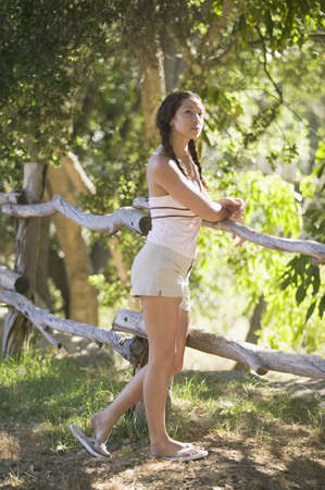 Woman leaning against forest fence Stock Photo - 16070843