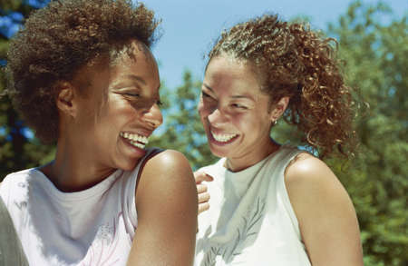 african ethnicity: Women friends sharing a laugh LANG_EVOIMAGES
