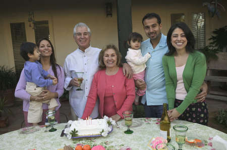 Portrait of a family standing in front of cake at a birthday party Stock Photo - 16070857