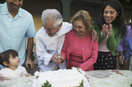 three generation: Older couple cutting cake as family celebrates