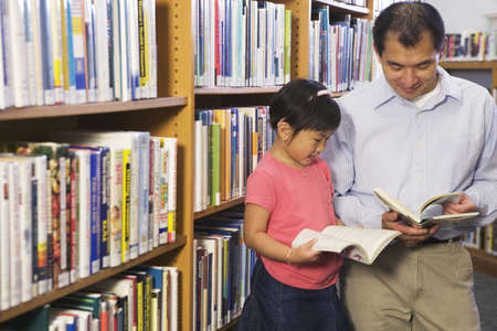 well read: Father and daughter looking at library books