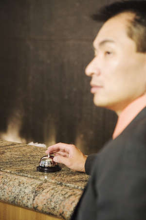 Man ringing service bell on counter Stock Photo - 16070864