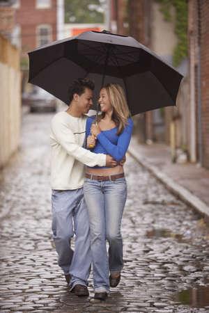 minority couple: Couple walking together under umbrella