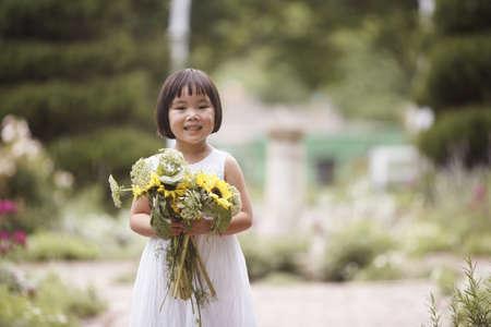 all under 18: Girl in garden holding flowers LANG_EVOIMAGES