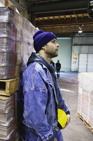 Man in warehouse leaning against pallet Stock Photo - 16043285