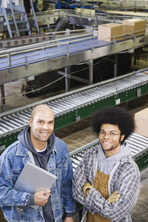 Two men standing in front of conveyor belt Stock Photo - 16070902