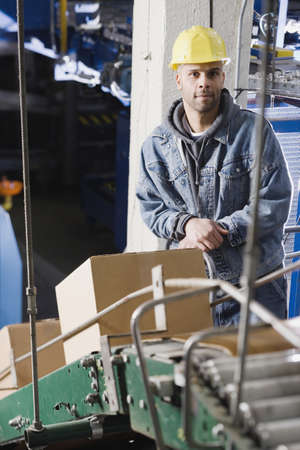 industrial machinery: Man standing behind conveyor belt