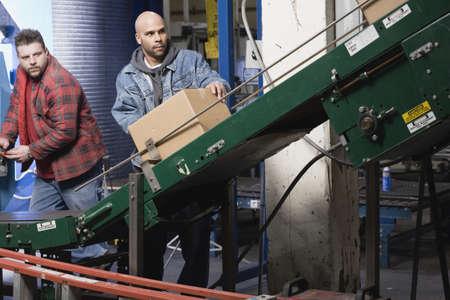cinta transportadora: Dos hombres de la correa transportadora funcionando LANG_EVOIMAGES