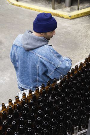 Man standing next to conveyor belt with bottles Stock Photo - 16043273