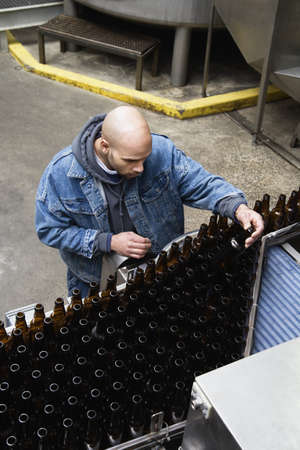Man inspecting bottles on conveyor belt Stock Photo - 16070914