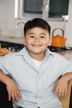 kitchen counter: Boy sitting at kitchen counter