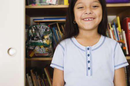 Girl standing in front of bookshelves Stock Photo - 16070936