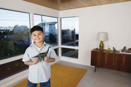 furnishings: Boy holding toy dinosaur